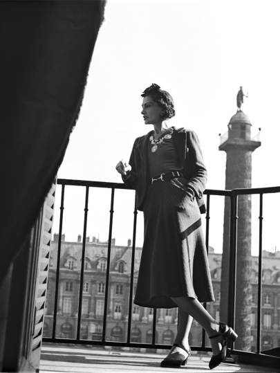 Coco Chanel standing on the balcony of her suite at The Ritz Paris, 1937