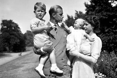 The Duke of Edinburgh, holding Prince Charles, with Princess Anne in the arms of Princess Elizabeth, in the grounds of Clarence House, 1951